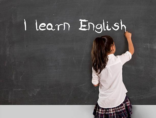 Niña en edad escolar escrito que aprender inglés con en pizarra de tiza - foto de stock