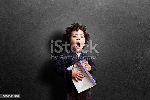 istock Schoolgirl yawning in classroom during study 539205383