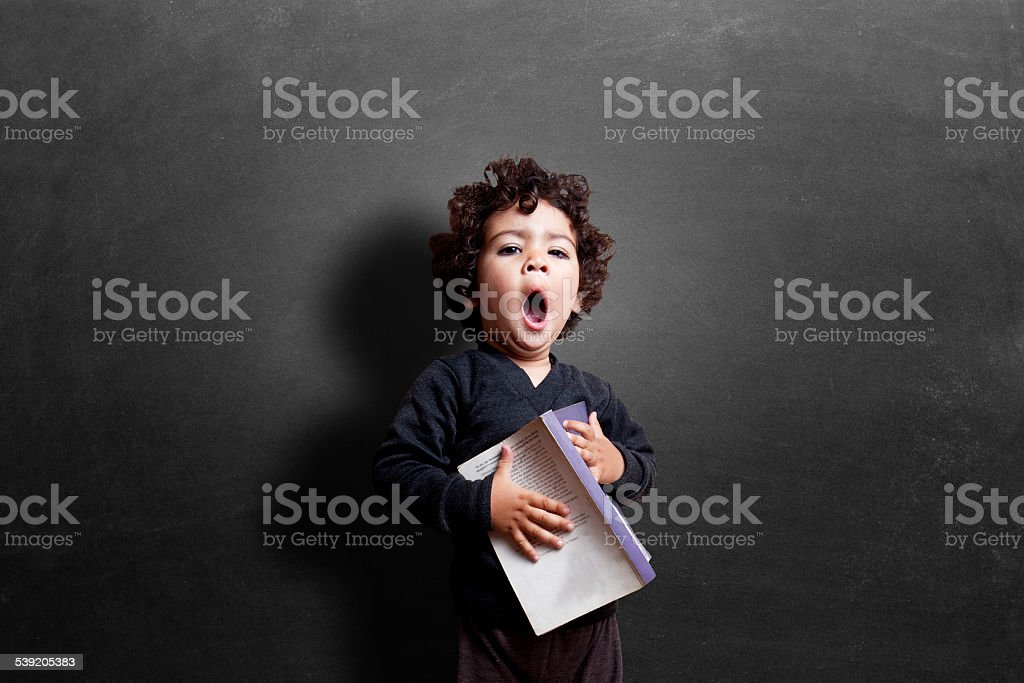 Schoolgirl yawning in classroom during study stock photo