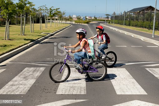 Side view of a Caucasian and an African American schoolgirl, both wearing cycling helmets and riding bicycles, crossing the road on a pedestrian crossing, on their way to elementary school on a sunny day