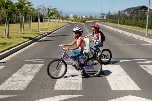 Schoolgirls crossing the road with bicycles stock photo