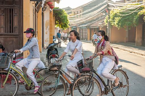 Schoolgirls drive bicycles to the schoot in Hoi An, Vietnam