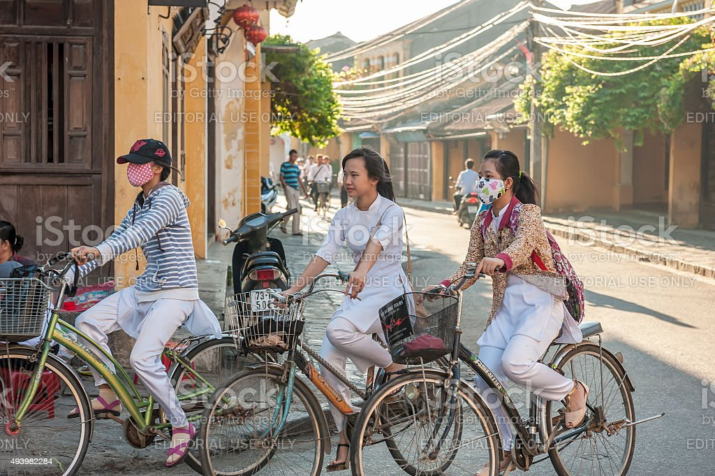 Schoolgirls drive bicycles to the schoot in Hoi An, Vietnam stock photo