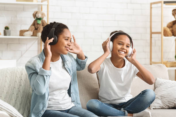 Schoolgirls listening to music with wireless headphones and dancing Two afro schoolgirls listening to music with wireless headphones and dancing at home, empty space wireless headphones stock pictures, royalty-free photos & images