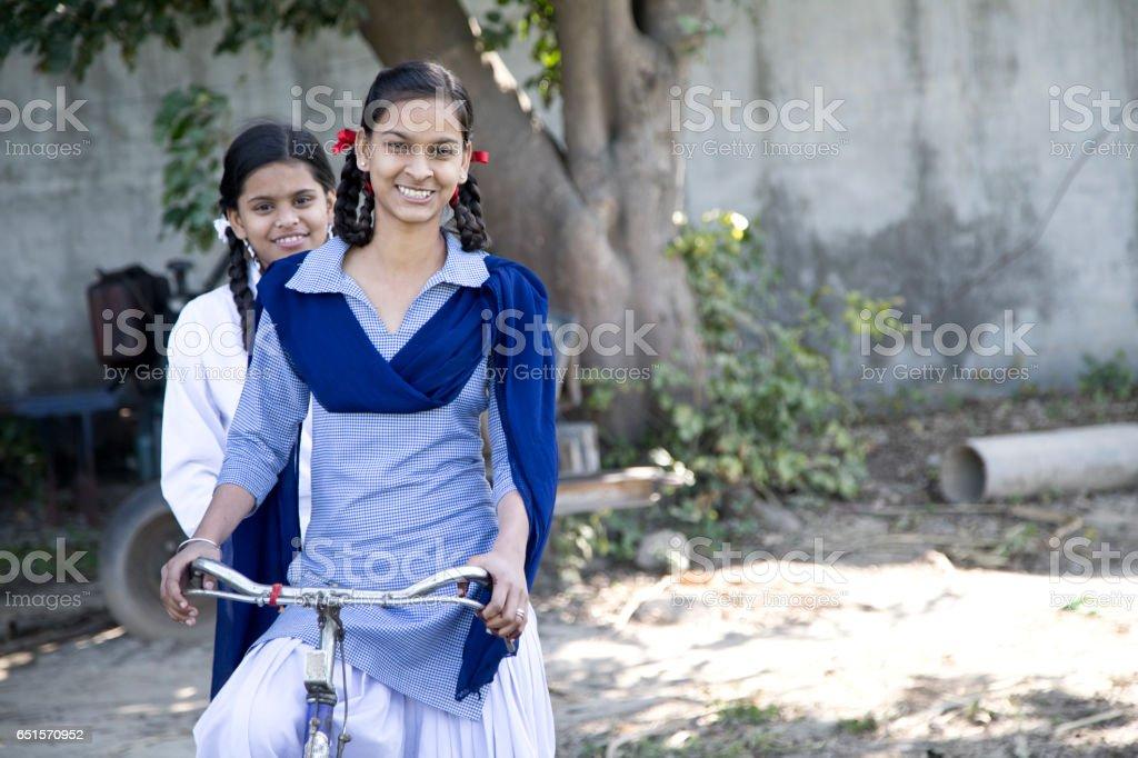 Schoolgirls on bicycle stock photo