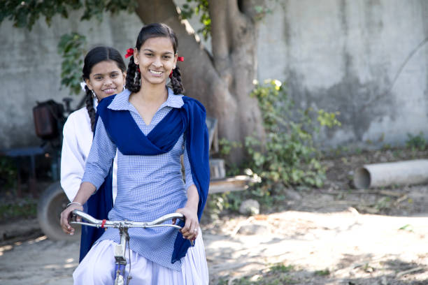 schoolgirls on bicycle - village stock photos and pictures