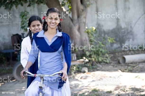 Portrait of Indian girls in school uniform on bicycle