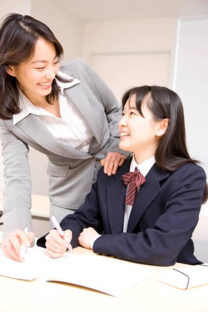 中学生が塾講師の勉強を教わり - 中学校 ストックフォトと画像