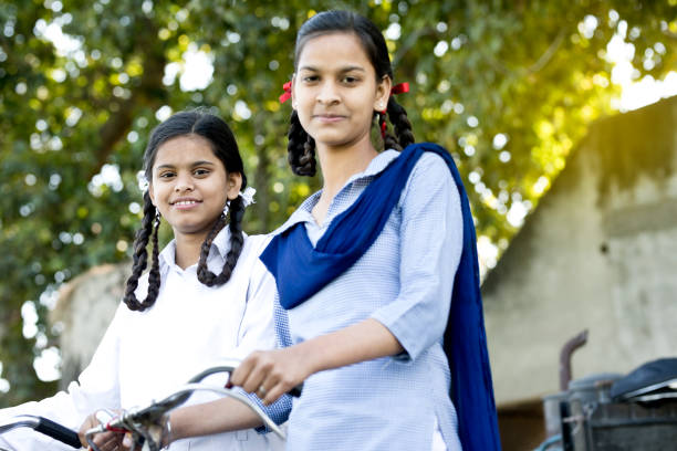 schoolgirls with bicycle - village stock photos and pictures