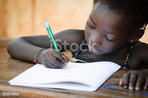 istock Schooling Symbol - African Young Girl Writing Notes 522079923