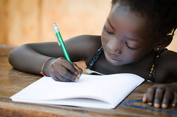 Schooling Symbol - African Young Girl Writing Notes A young African girl writing her lesson on a sheet of paper. developing countries stock pictures, royalty-free photos & images