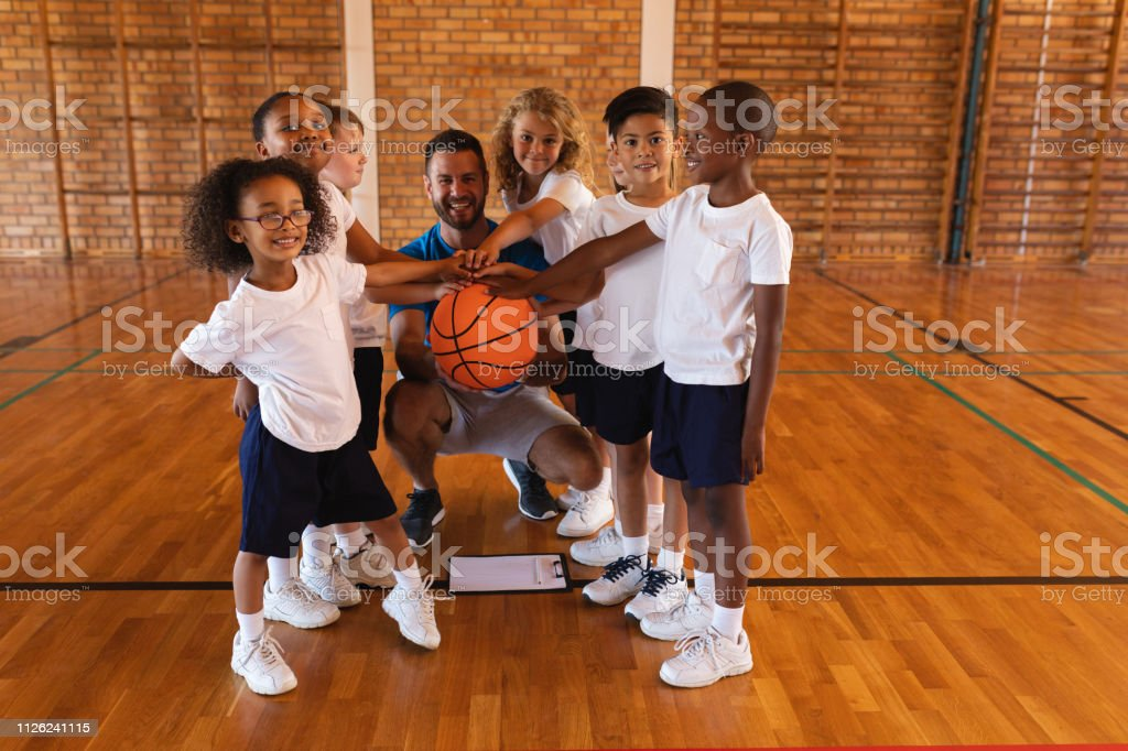 Happy schoolkids and basketball coach forming hand stack and looking...
