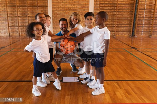 Happy schoolkids and basketball coach forming hand stack and looking at camera in basketball court