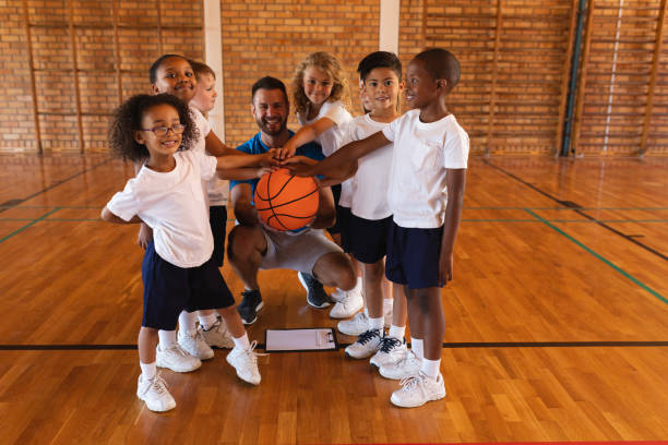 schoolkids and basketball coach forming hand stack and looking at camera in basketball court - infanzia foto e immagini stock