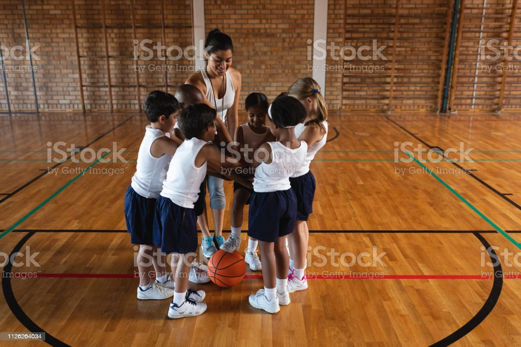 Front view of schoolkids and female coach forming hand stack at...