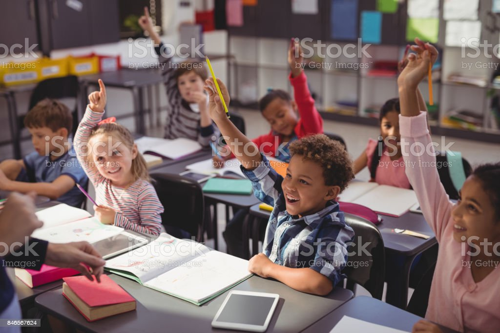 Schoolkids raising their hands in classroom royalty-free stock photo