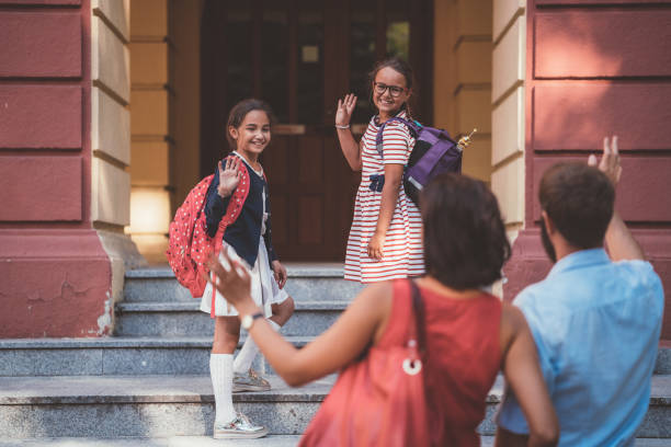 Schulkindern, die winken mit der Hand an ihre Eltern vor dem Eintritt in das Schulgebäude – Foto