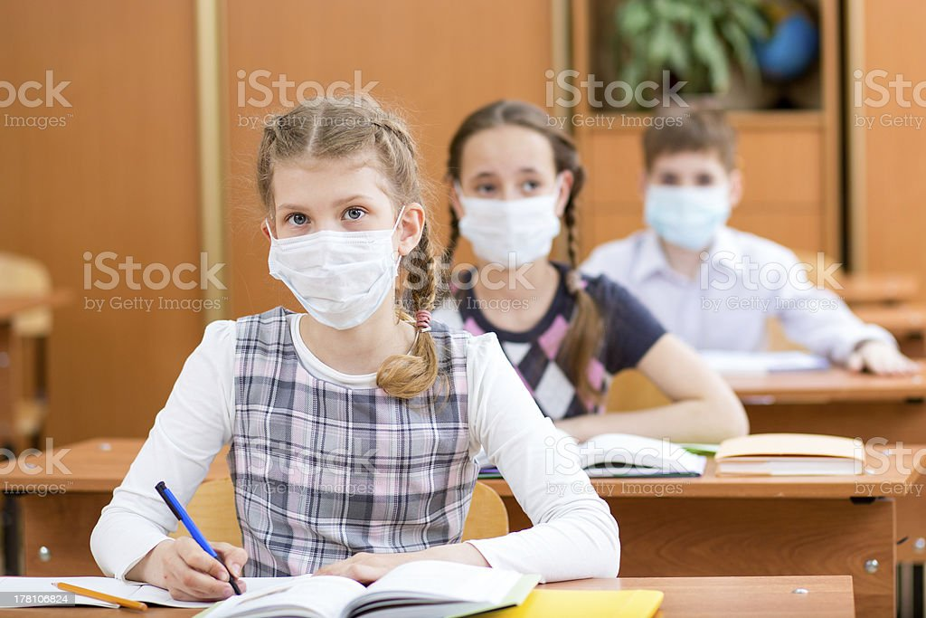 schoolkids with protection mask against flu virus at lesson schoolkids with protection mask against flu virus at lesson Boys Stock Photo