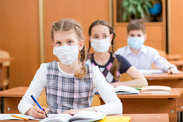 schoolkids with protection mask against flu virus at lesson stock photo