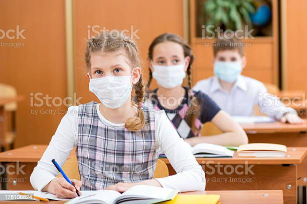 Schoolkids With Protection Mask Against Flu Virus At Lesson Stock Photo - Download Image Now
