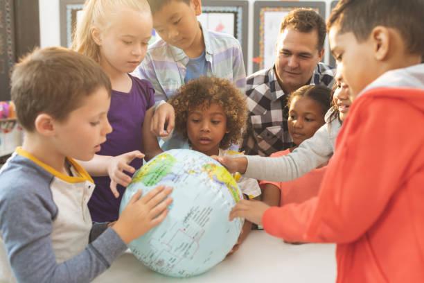 schullehrer im unterricht in der schule über einen erdball - kartographie stock-fotos und bilder