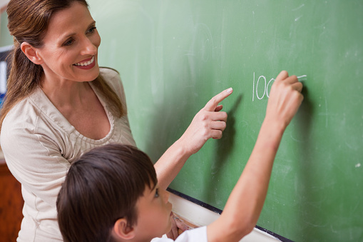 istock Schoolteacher helping a schoolboy doing an addition 827842756