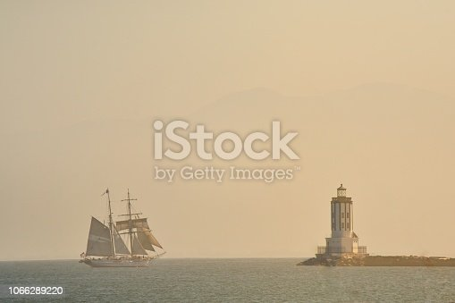The Los Angeles harbor lighthouse at Cabrillo Beach is approached by a two masted sailing ship with a mountain ridge obscured in the background