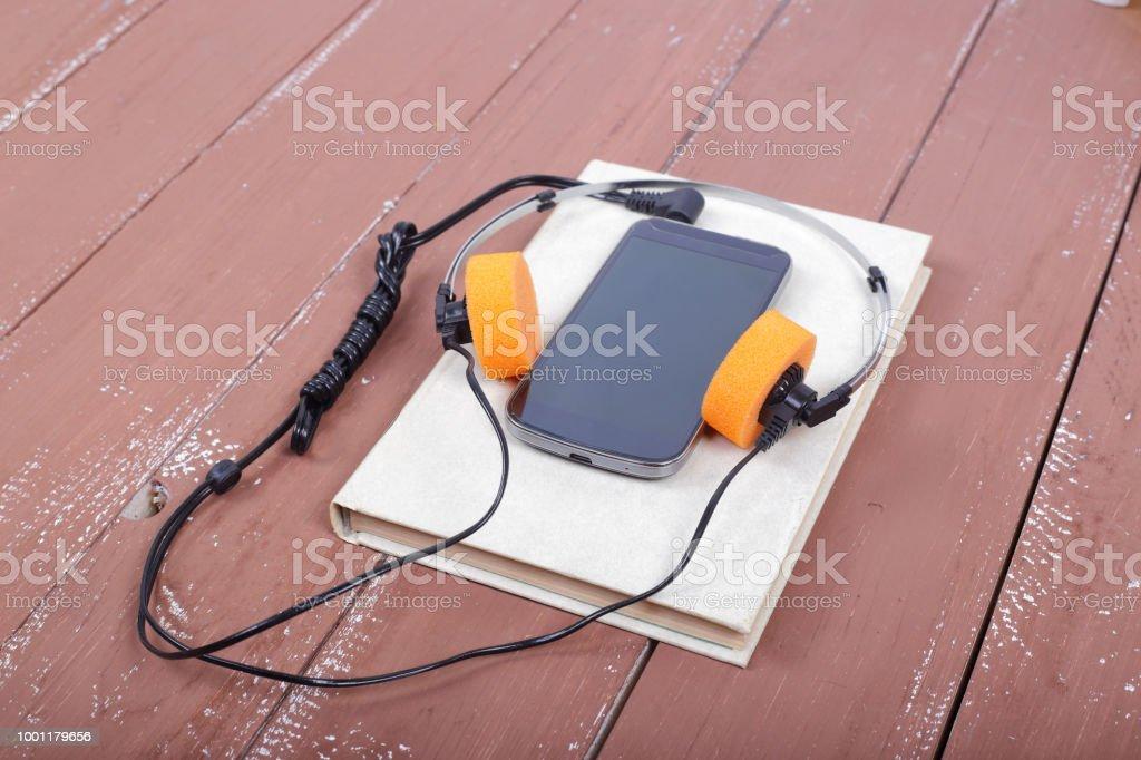 Ciência e educação - Audiobook Smartphone na mesa de madeira - foto de acervo