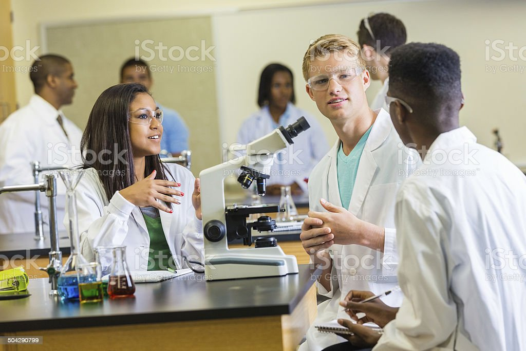 Science classmates discussing assignment while using microscope stock photo