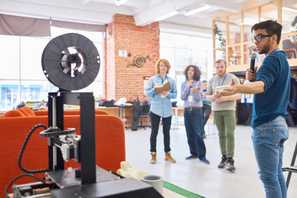Science exhibition Hispanic specialist telling about opportunities of 3D printer to students at scientific conference college fair stock pictures, royalty-free photos & images