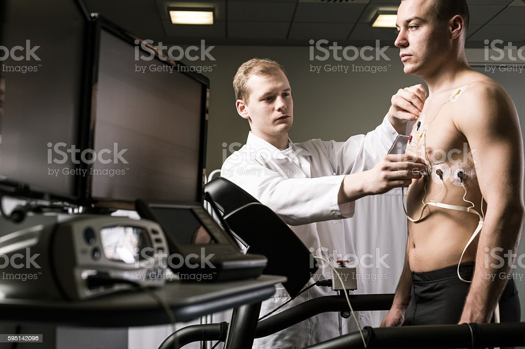 Doctor is preparing a sportsman to the medical trial
