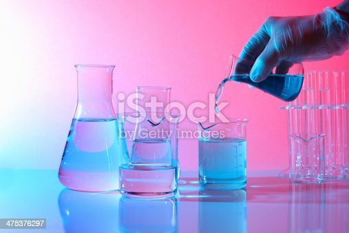 1097010784istockphoto Science laboratory, hand picking flask pouring blue liquid, test tubes 475376297