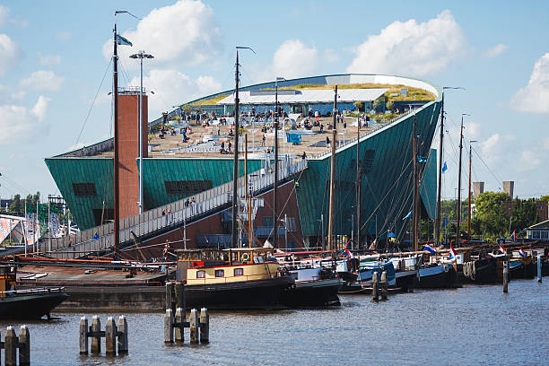 NEMO Science Museum, Amsterdam Amsterdam, Netherlands - July 2, 2016: Some people visit of NEMO Science museum, view from Oosterdok street, sunny day nemo museum stock pictures, royalty-free photos & images