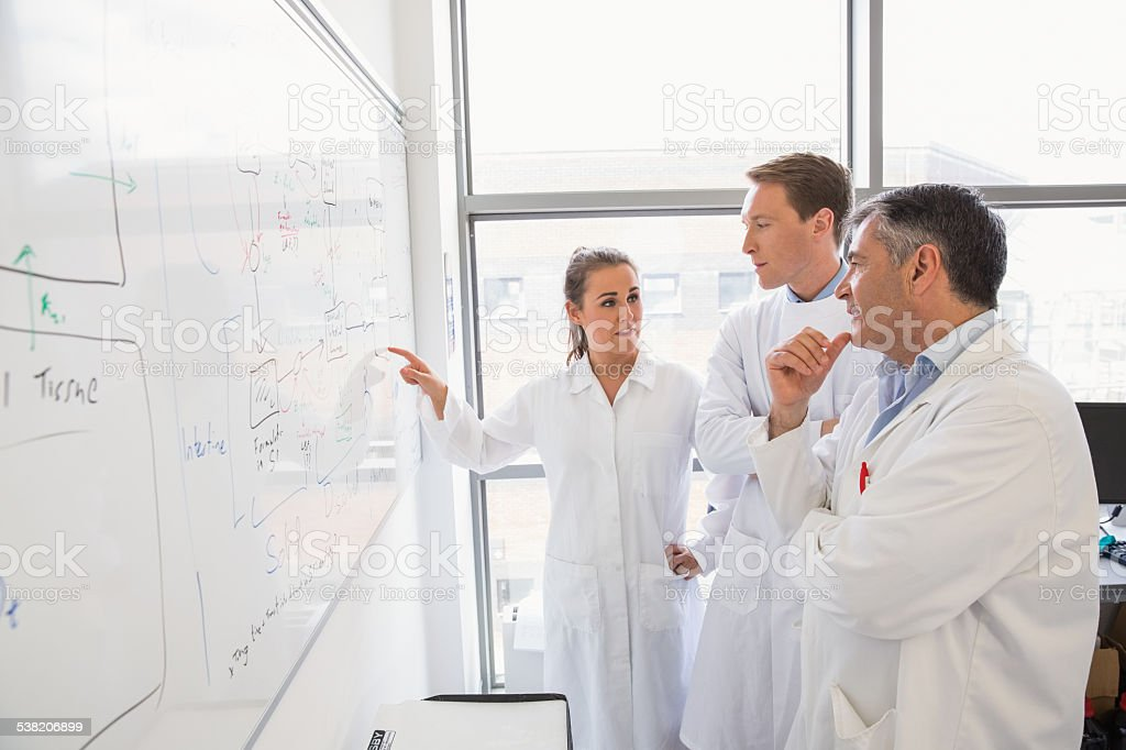 Science students and lecturer looking at whiteboard stock photo