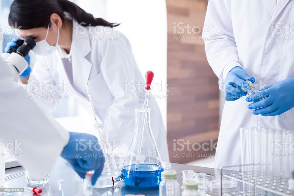 Science students working with chemicals in lab at the university.