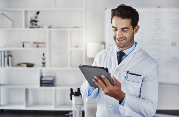 Science sure has advanced a long way Shot of a scientist using a digital tablet while working in a lab lab coat stock pictures, royalty-free photos & images