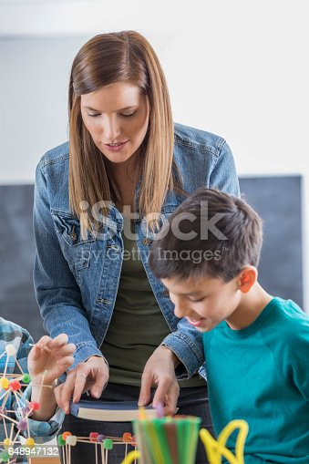 648947070 istock photo Science teacher helps students with assignment 648947132