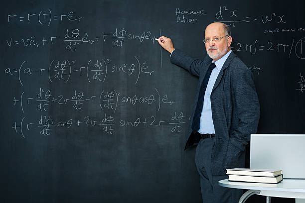 Science teacher writting at blackboard physics equation stock photo