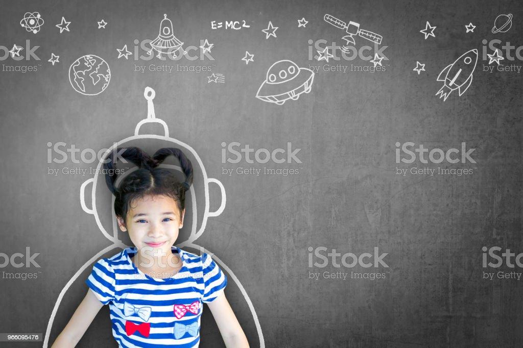 Science technology engineering maths STEM education concept with school girl kid in astronaut helmet and creative innovative knowledge learning doodle on teacher's chalkboard - Стоковые фото Азиатского и индийского происхождения роялти-фри