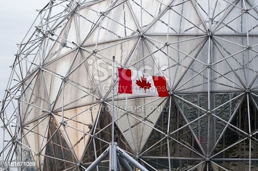 Vancouver, BC, Canada - Oct 12, 2019: Close up of Science World's iconic geodesic dome with waving Canadian flag in the front.