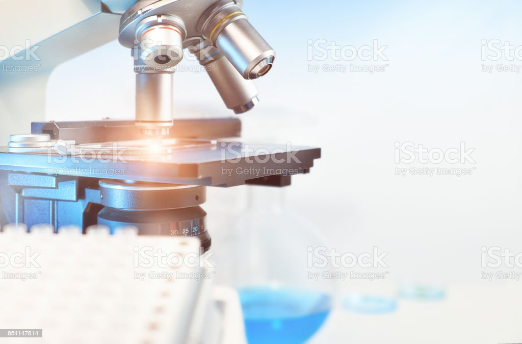 Scientific background with closeup on light microscope and blurred laboratory stock photo