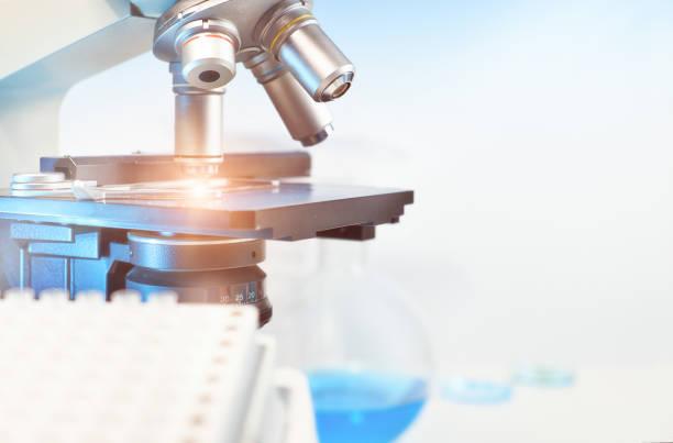 光学顕微鏡とぼやけている所にクローズ アップと科学的背景 ストックフォト