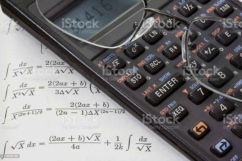 scientific calculator, reading glasses, math book background royalty-free stock photo