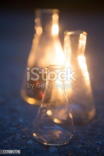 Erlenmeyer flask backlit on concrete.