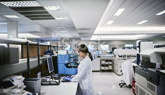 Shot of a young woman using a computer while working in a laboratory