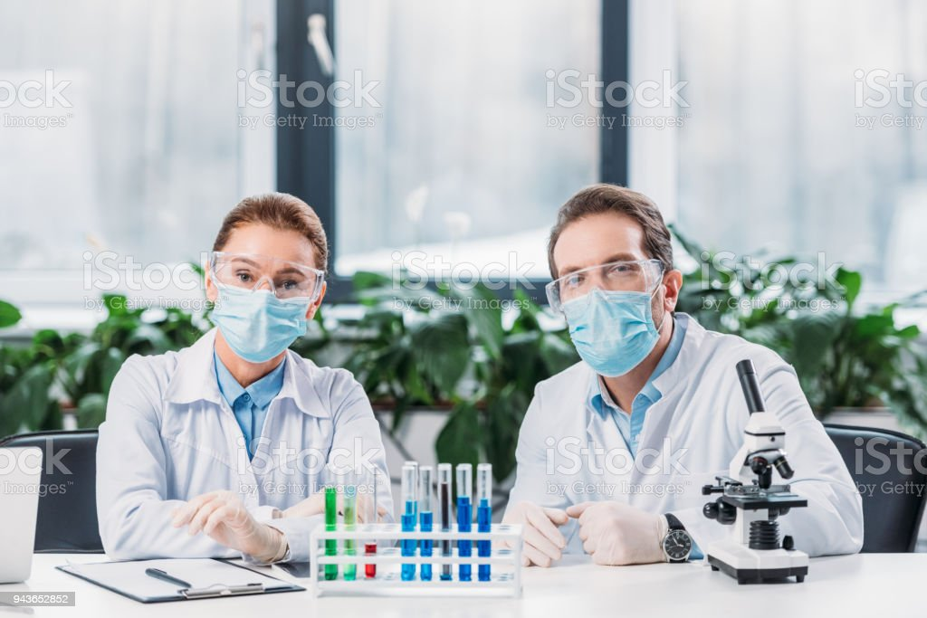 scientific researchers in goggles and medical masks sitting at workplace with reagents in tubes and microscope in lab stock photo