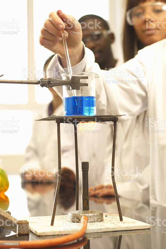 Scientist adding solution to beaker stock photo
