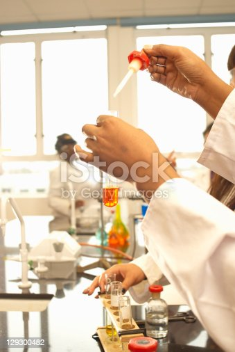 129300487 istock photo Scientist adding solution to test tube 129300482