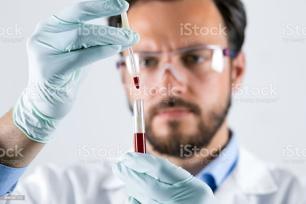 scientist analyzing blood test sample in laboratory stock photo