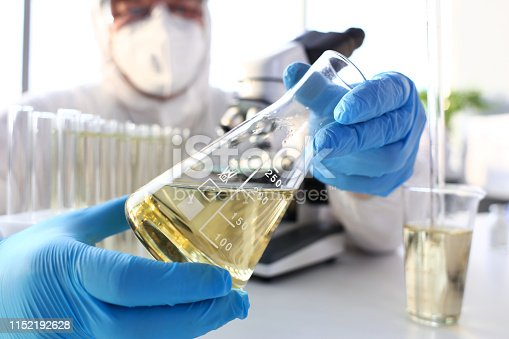 Scientist arm in protective gloves hold yellow liquid in bottle closeup
